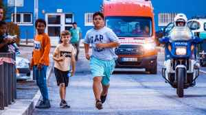 boy runs at the street while people looking at him