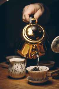 person holding gold teapot pouring white ceramic teacup